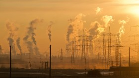 A photograph of a coal-fired power station under a hazy orange sky.