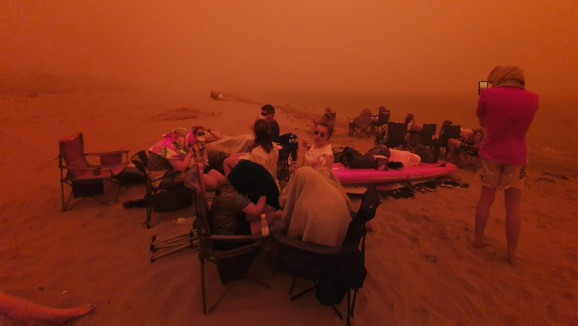 People evacuating from bushfires in a red haze at Batemans Bay beach on New Year's Eve, 2019