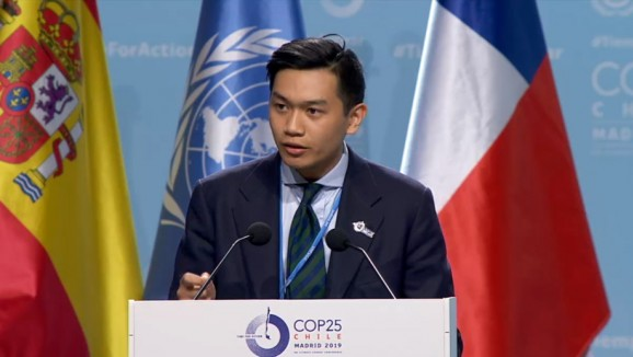 PhD student, Aaron Tang speaking at a lectern at the official Researchers and Independent NGOs statement at the COP25 with several flags in the background