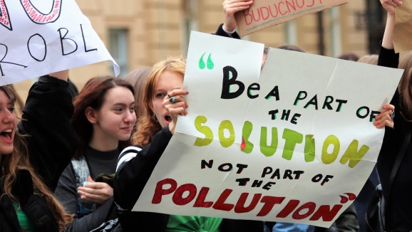 A group of young climate protesters holding placards