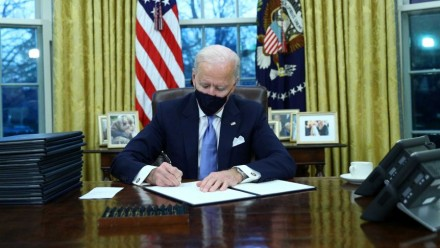 A photograph of US President Joe Biden signing Executive Orders in the Oval Office on his first day in office.