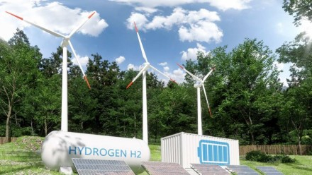 A picture of small wind turbines, solar panels, and hydrogen tanks in a green field, with trees and a blue sky behind.
