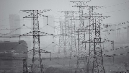 A photograph of many power lines altogether, in an industrial area covered in heavy smog.