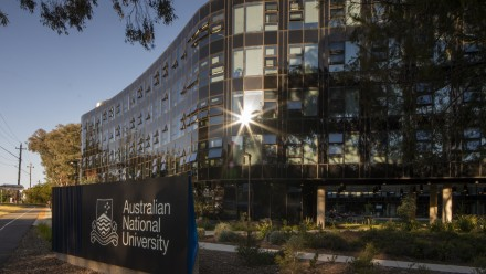 A photograph of the Australian National University sign in front of Warrumbul Lodge on the ANU Acton campus.