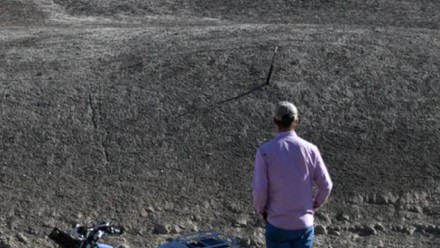 A man standing next to a motorbike, looking at a dried out river bed.