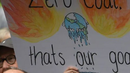 A sign being held up at a climate change protest, reading 'Zero coal - that's our goal', and a drawing of Earth melting as though it was an icecream.