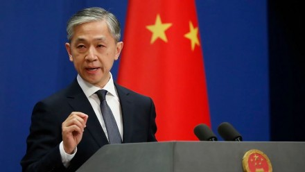An image of Chinese Foreign Ministry spokesman Wang Wenbin giving a speech at a podium, with a dark blue background and the Chinese flag hanging in the corner.