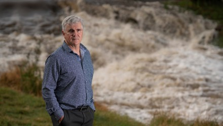 A photograph of Prof Mark Howden, standing looking towards the camera, with Sullivans Creek behind him.