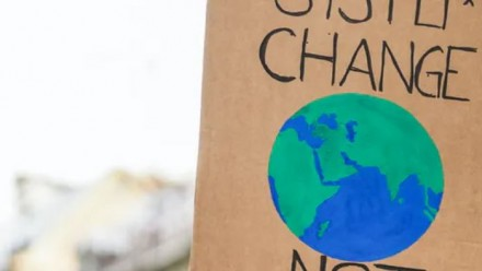 A cardboard sign being held up at a climate protest, with a painting of the Earth in the middle.