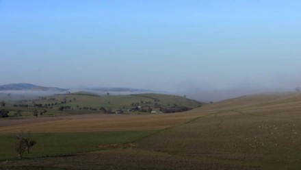 A photograph of green rolling hills, with a slight mist above them.