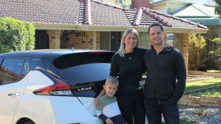 A photograph of the Dudney family standing next to their white car, in front of their beige brick house.