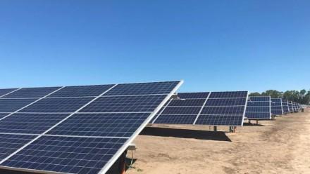 A photograph of a solar farm on top of a dusty, dry area, on a clear sunny day.