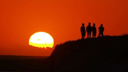 A photograph of three people standing on a hill watching the sun set.