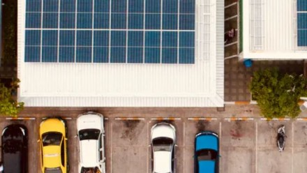An aerial photograph of cars parked next to a building with solar panels on its roof.