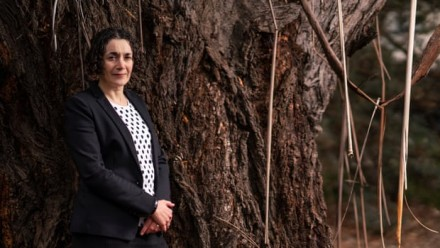 A photograph of Dr Joelle Gergis, leaning against a tree and looking towards the camera.
