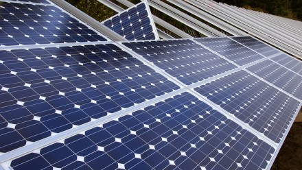 A photograph of solar panels being installed on a roof.