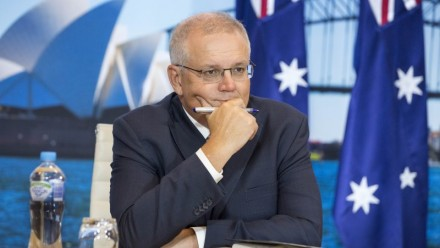 A photograph of Scott Morrison sitting at a desk looking to the right of the camera, with a picture of the Sydney Opera House and two Australian flags behind him.