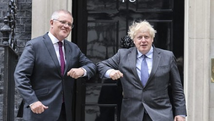 A photograph of UK Prime Minister Boris Johnson and Australia's Prime Minister Scott Morrison bumping elbows together (as a COVID-19 safe form of a handshake) in front of Number 10 Downing Street.
