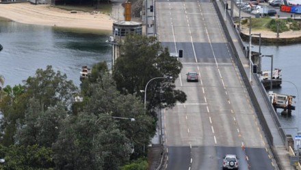 An aerial photograph of a road with only two cars driving on it.