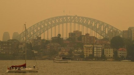 A photograph of Sydney Harbour Bridge, shrouded in orange bushfire smoke
