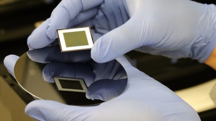 A close-up photograph of a person with gloved hands holding a bifacial silicon solar cell.