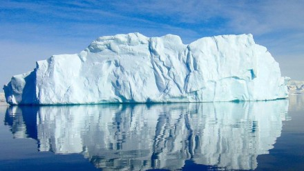 A large iceberg sits in ocean waters in the Antarctic region