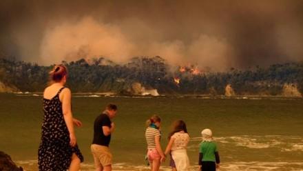 Evacuees on a beach look on as bushfire burns through the NSW south coast township of Malua Bay.