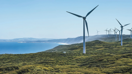 Wind turbines along a coastal cliff, with a view of the ocean in the distance.