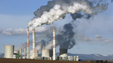 A photograph of a coal fired power station, with smoke billowing out of the chimneys.
