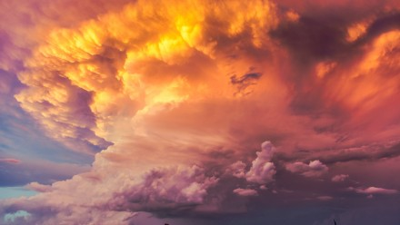 A photograph of a towering cloud, coloured oranges and pinks by the setting sun.