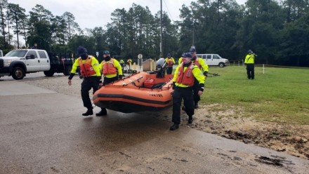 A photograph of a team of rescue workers in high-vis clothing carrying an inflatable boat.