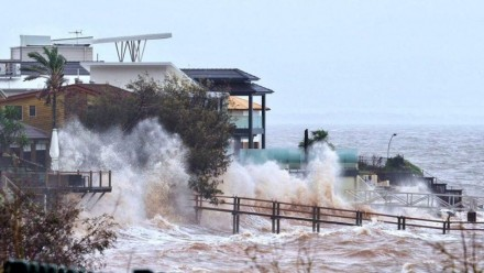 Waterfront homes at Scarborough in the Moreton Bay region being lashed by wild weather and big swells.