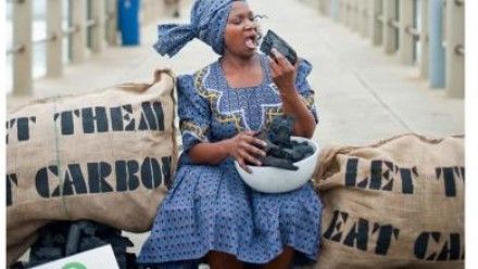 A woman holds a block of coal up to her mouth as though she is about to eat it, with the words 'let them eat carbon' on the hessian bags behind her.