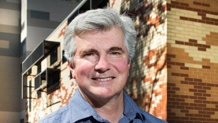 A photograph of Prof Mark Howden standing outside the Frank Fenner building at The Australian National University, smiling and looking at the camera.
