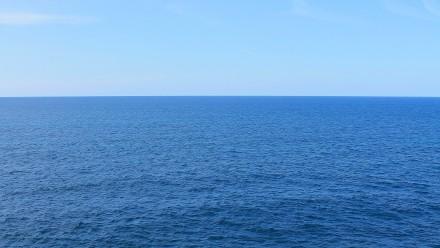 An aerial photograph of the ocean, underneath a clear blue sky.