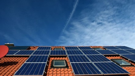A photograph of solar panels on a red tile roof, with a blue sky above.