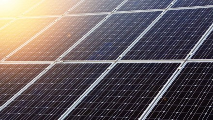 A photograph of solar panels, with the sun shining from the top left corner.