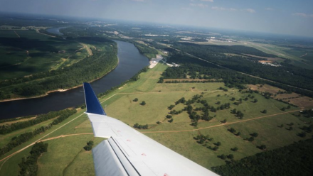 The view out of a plane window, with the plane wing slanting across the image, and green fields with a river running through them below.