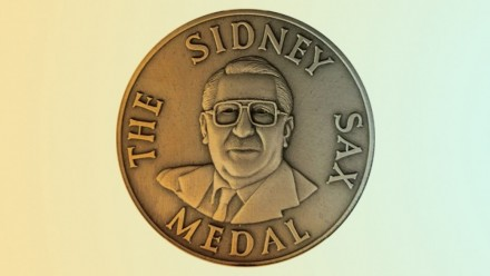 A photograph of the Sidney Sax medallion, with the words 'The Sidney Sax Medal' around the outside, and an engraving of Sidney Sax in the middle.