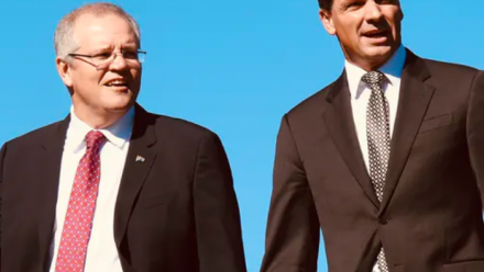 Scott Morrison and Angus Taylor walking together, with a background of a clear blue sky.
