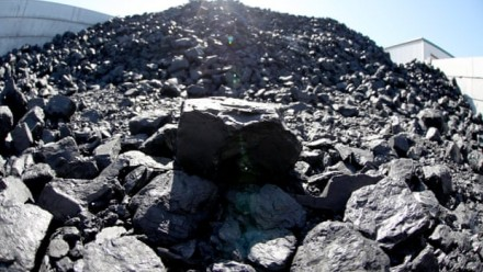 A close-up image of a mound of coal, with the sun shining and a blue sky behind.