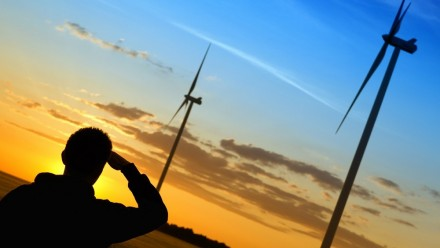 Silhouette of a man looking at wind turbines during sunset