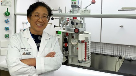 Professor Yun stands in her lab, in front of the hydrogenation reactor that enables hydrogen to be released from liquid organic carriers