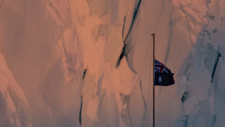 A photograph of the Australian flag flying in Antarctica, with a sheet of ice behind it that appears faintly pink due to the setting sun.