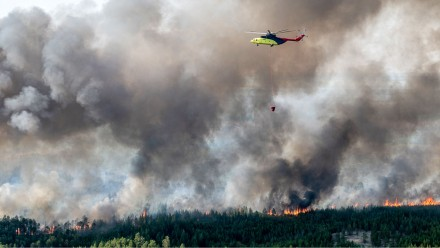 A photograph of a helicopter dropping water on a wildfire in Siberia