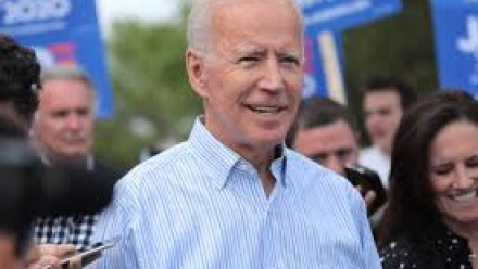 A photograph of Joe Biden standing outdoors, surrounded by supporters, smiling and looking past the camera.