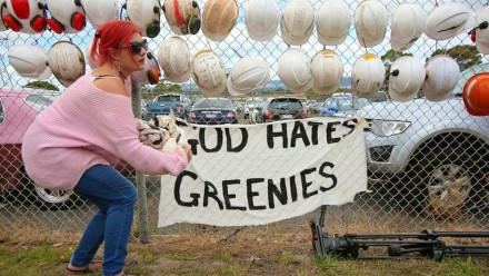 A photograph of someone standing next to a sign reading 'God Hates Greenies' on a fence, with protective hard hats hung on the fence alongside it.