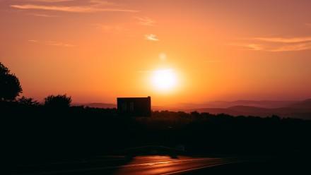 A photograph of the sun setting over a city, with a hazy, orange sky.