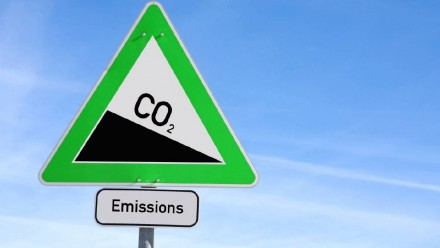 An image of a triangle road sign, with CO2 written on it on a downwards slope, and 'emissions' written beneath it.