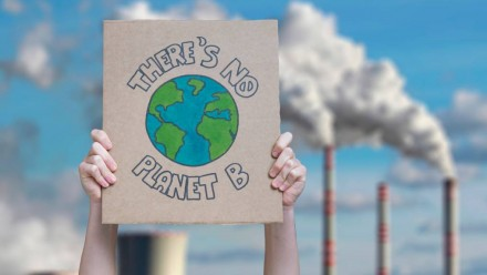 Someone holding up a sign in front of a coal-fired power station that says 'there is no planet B'